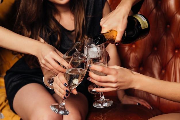 Frau gießt weißen champagner in gläser. nahansicht