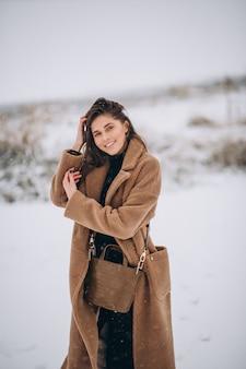 Frau glücklich im mantel im winter draußen im park