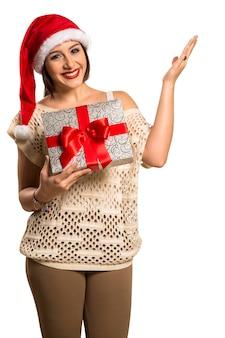 Frau glückliches lächeln punktfinger zeigt seite leeren kopierraum, junge aufgeregte frau tragen weihnachtsmütze, werbeprodukt isoliert