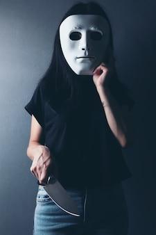Frau greift mit einem küchenmesser in einer anonymen maske an