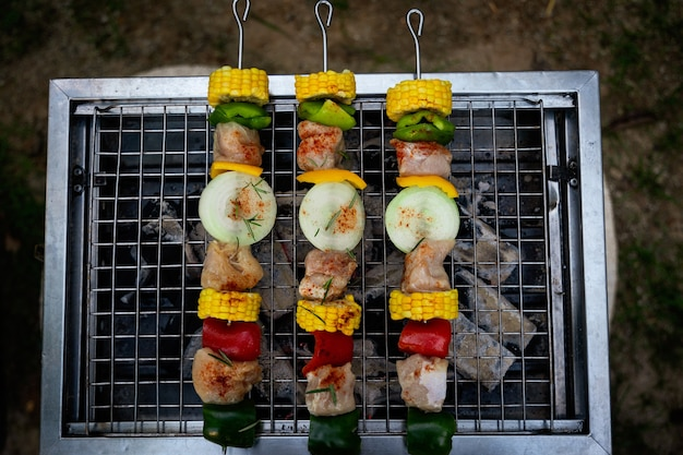 Frau grillt fleisch- und gemüsespieße auf riesigen auf der kohlenpfanne frau kocht fleisch auf grill