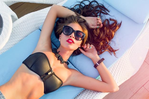 Frau haben ein sonnenbad und entspannen auf einer sonnenliege