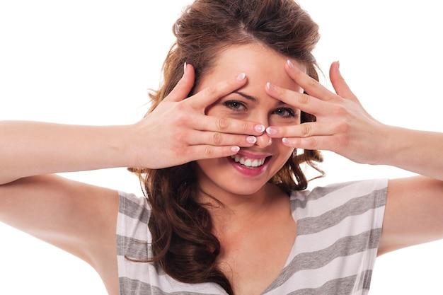 Frau haben spaß, indem sie sich hinter ihren fingern versteckt
