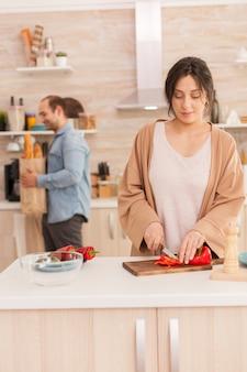 Frau hackt gemüse für salat auf schneidebrett und ehemann ist mit lebensmittelbeutel im hintergrund. lustiges glückliches verliebtes paar zu hause, das zeit zusammen verbringt, gesund kocht und lächelt