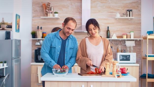 Frau hackt paprika auf schneidebrett und ehemann öffnet kühlschranktür. kochen, das gesundes bio-lebensmittel glücklich zusammen lebensstil zubereitet. fröhliches essen in der familie mit gemüse