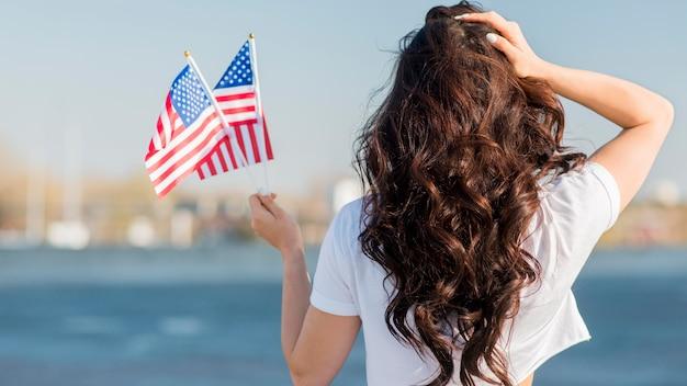 Frau hält 2 usa-flaggen von hinten