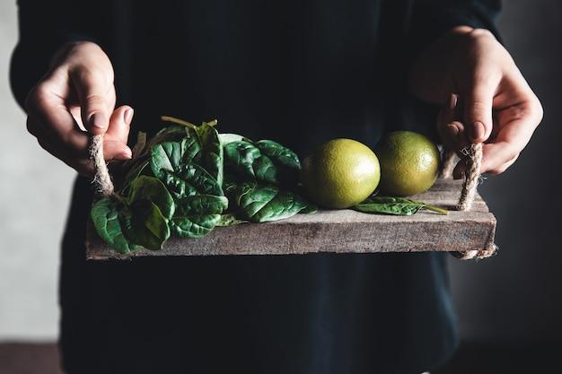 Frau hält auf einem vintage-tablett einen spinat mit limette