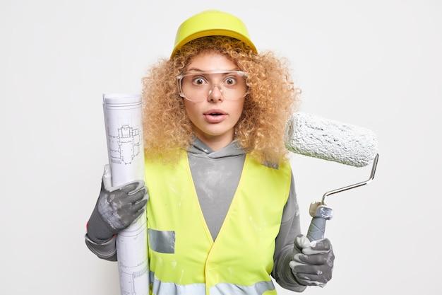 Frau hält blaupause und walze bietet professionelle servicearbeiten in der wohnung an, die frische malerei erfordert