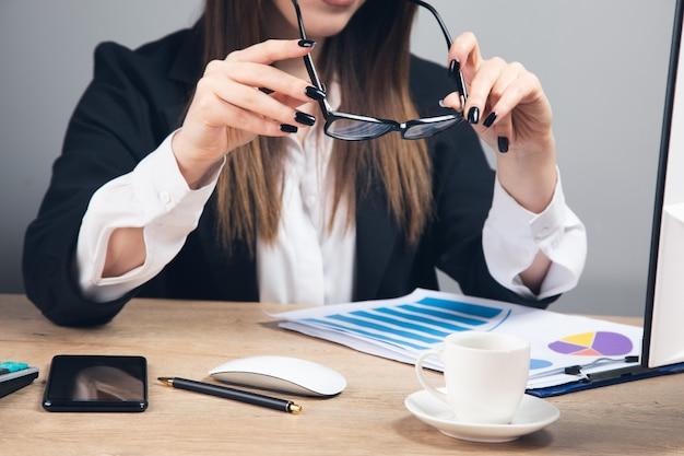 Frau hält brille und liest finanzbericht