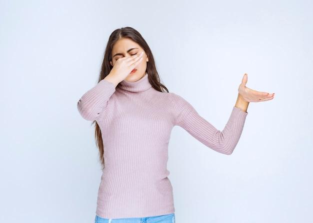 Frau hält den atem wegen schlechten geruchs an.
