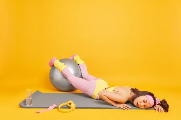 Frau hält den fitnessball in den händen und fühlt sich nach müdem training in activewear sehr müde, liegt auf karemat