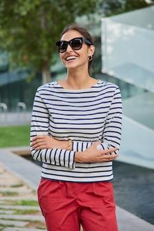 Frau hält die arme verschränkt und lächelt breit trägt eine sonnenbrille, einen gestreiften pullover und eine rote hose wirft spaziergänge im freien während des frühlingstages auf der straße auf unscharf