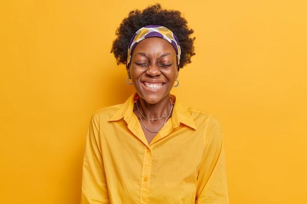 Frau hält die augen geschlossen lacht glücklich kichert unbeschwert zeigt weiße zähne trägt stirnband und hemd isoliert auf leuchtendem gelb
