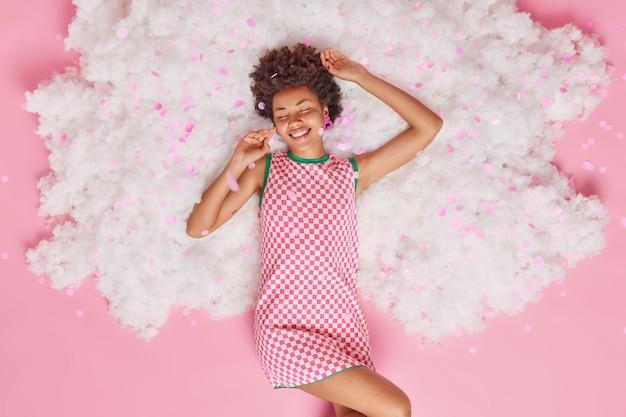 Frau hält die augen vor vergnügen geschlossen trägt kleid genießt freiheit und entspannung posiert auf weißer wolke mit fliegendem konfetti auf rosa