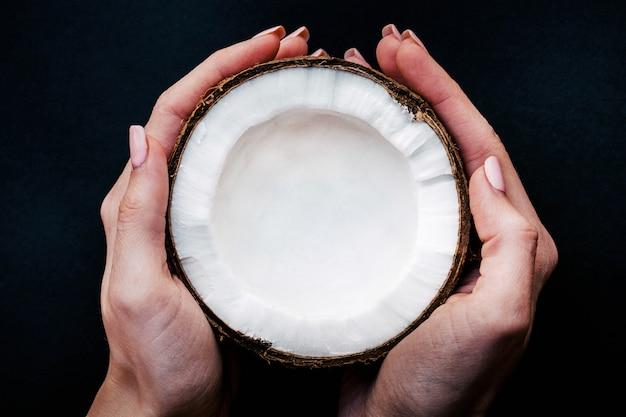 Frau hält die hälfte einer kokosnuss