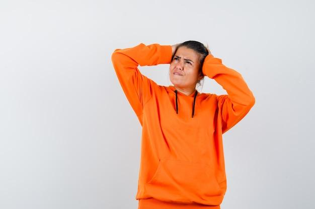 Frau hält die hände auf dem kopf in orangefarbenem hoodie und sieht vergesslich aus