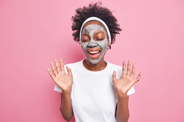 Frau hält die hände erhoben, hat spaß, trägt eine pflegende tonmaske für die hautpflege auf, trägt ein stirnband und ein lässiges weißes t-shirt isoliert auf rosa