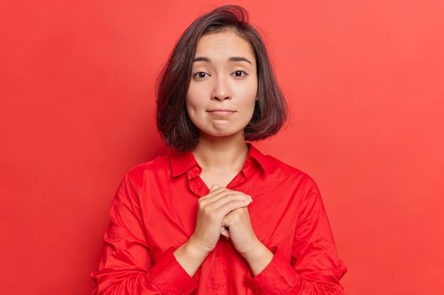 Frau hält die hände in gebetsgeste zusammen hat mitleid ausdruck bittet um entschuldigung sieht mit großer hoffnung in die kamera trägt hemdposen auf leuchtendem rot