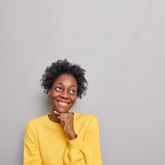 Frau hält die hand unter dem kinn schaut nach oben stellt sich vor, etwas trägt einen lässigen gelben pullover steht auf grau