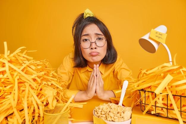 Frau hält die handflächen zusammengedrückt bittet um gunst, um ihr noch eine chance zu geben sitzt am schreibtisch, umgeben von geschnittenen papierstapeln auf gelb