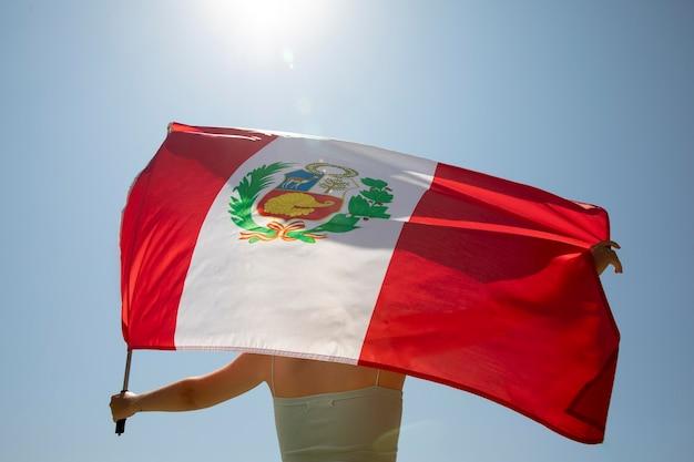 Frau hält die peru-flagge