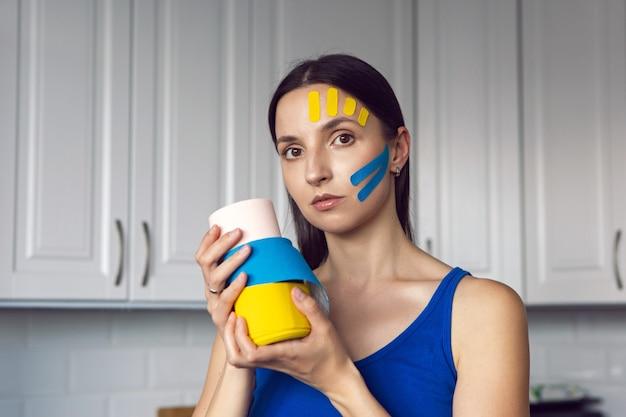 Frau hält drei stränge kinesio-tape in der hand gelb und blau