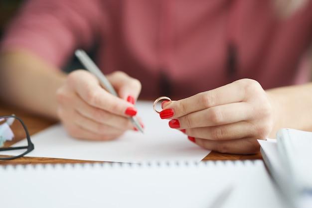 Frau hält ehering und schreibt aussage
