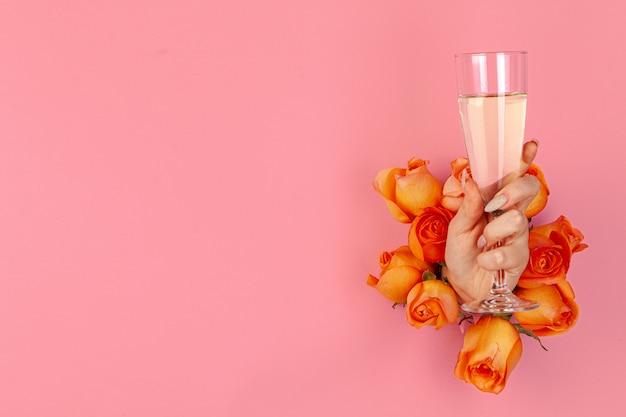 Frau hält ein glas champagner in der hand, das durch ein loch in rosa papier mit frischen rosen gesteckt wird