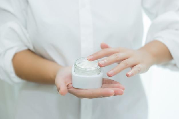 Frau hält ein glas mit einer kosmetischen creme in den händen