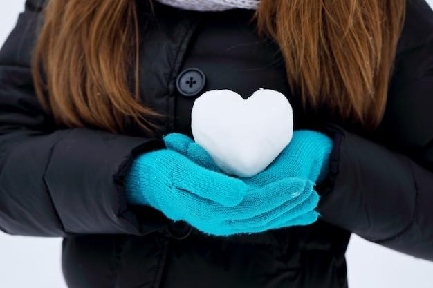 Frau hält ein herz aus schnee. das konzept des valentinstags