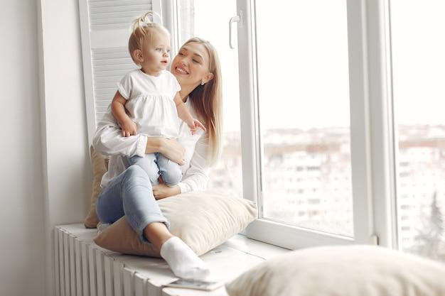 Frau hält ein kind in den armen und umarmt sie. mutter in einem weißen hemd spielt mit ihrer tochter. familie hat spaß an den wochenenden.