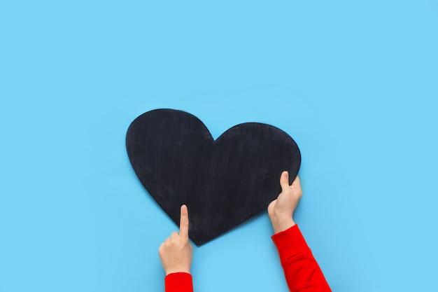 Frau hält ein kreidebrett in form eines herzens auf einem blauen hintergrund für valentinstag