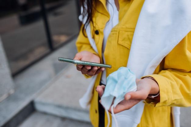 Frau hält ein smartphone und eine maske