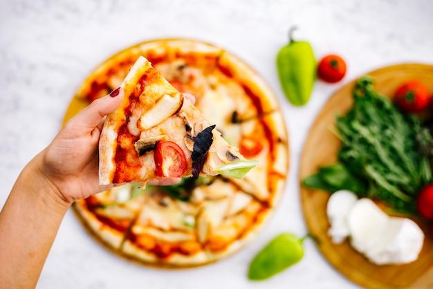 Frau hält ein stück hühnerpizza mit pilztomate mit kräutern belegt