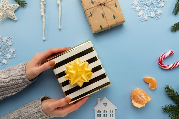 Frau hält ein weihnachtsgeschenk in ihren händen