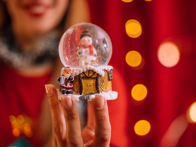 Frau hält ein weihnachtsspielzeug auf unscharfer roter wand