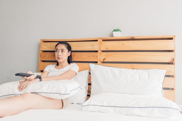 Frau hält eine fernbedienung und sieht ernsthaft drama-tv-serie.
