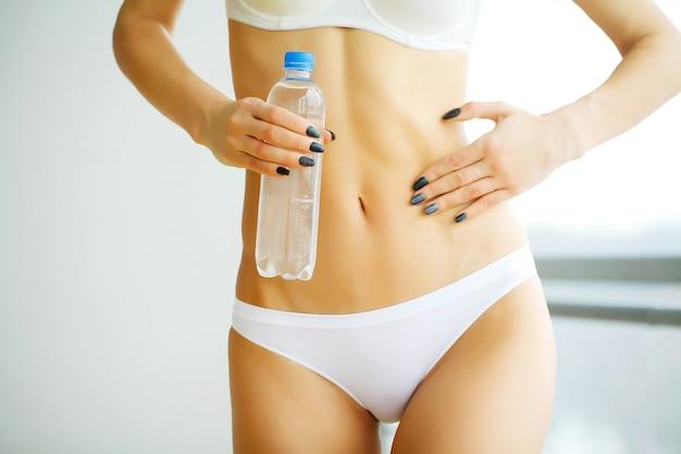 Frau hält eine flasche sauberes wasser in den händen.