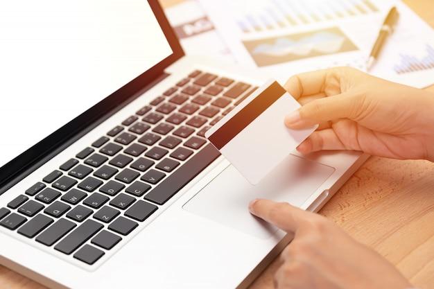 Frau hält eine kreditkarte und kauf online über den computer bezahlen