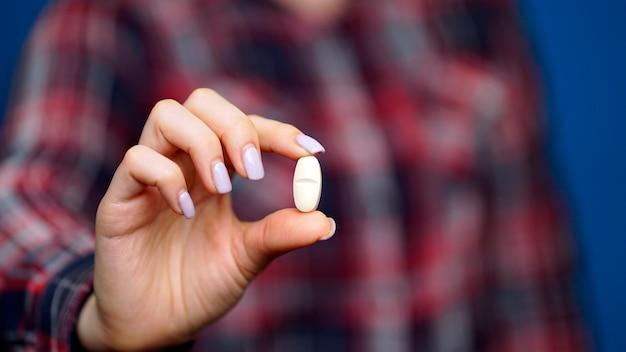 Frau hält eine pille in der hand