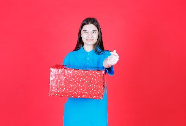 Frau hält eine rote geschenkbox mit weißen punkten darauf und bittet um zahlung.