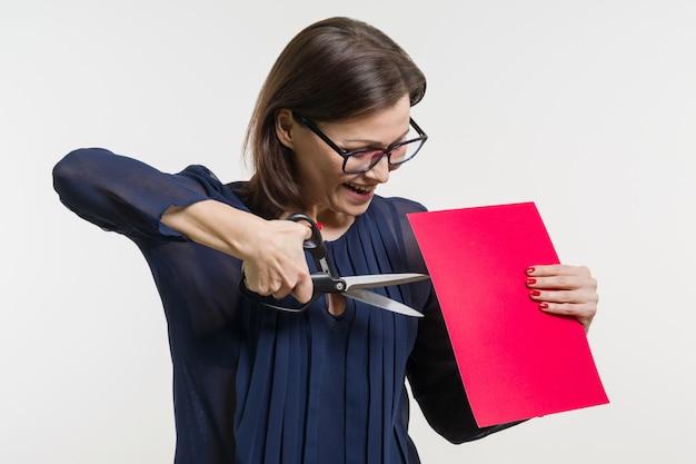 Frau hält eine schere und ein blatt papier, schneidet papier.
