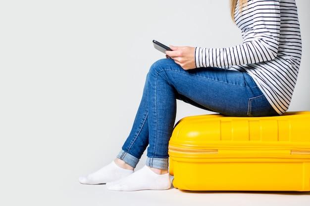 Frau hält eine tablette und sitzt auf einem gelben plastikkoffer auf einem hellen raum. reisekonzept, flugerwartung, urlaub.