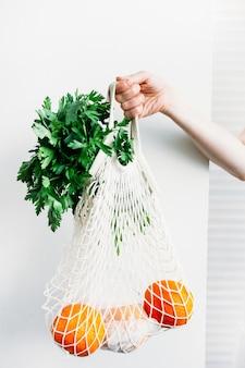 Frau hält eine tasche mit essen frischem gemüse und obst