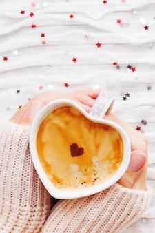 Frau hält eine tasse heißen kaffee mit zimtherzen.