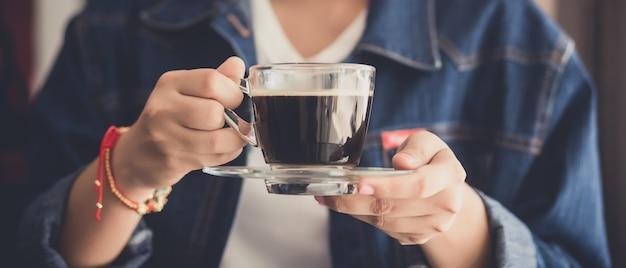 Frau hält eine tasse heißen kaffee