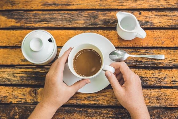 Frau hält eine tasse kaffee in einem straßencafé