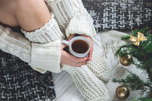 Frau hält eine tasse tee neben ihren beinen