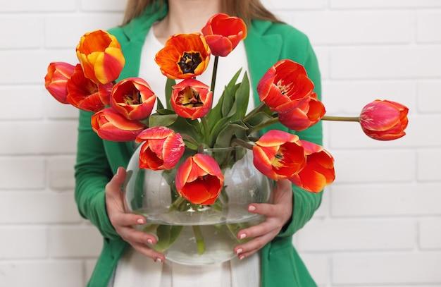 Frau hält eine vase mit tulpen