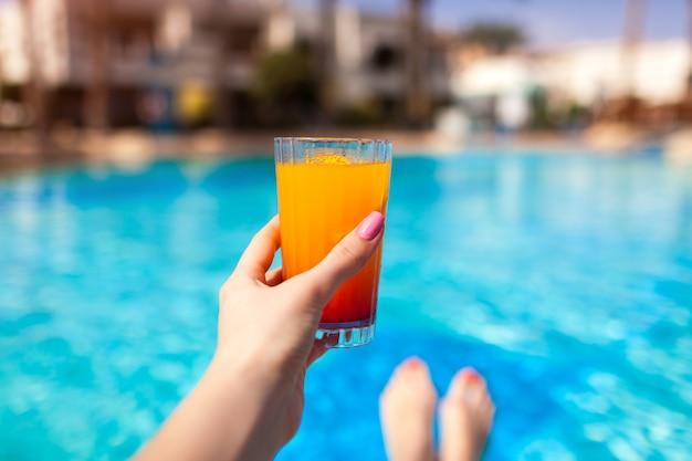 Frau hält einen cocktail am swimmingpool